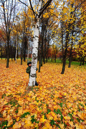 The Boy Hid Behind a Tree In Autumn Forest photo