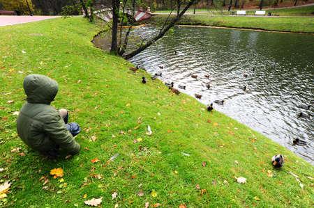 Boy Watching Wild Ducks In Autumn Park photo