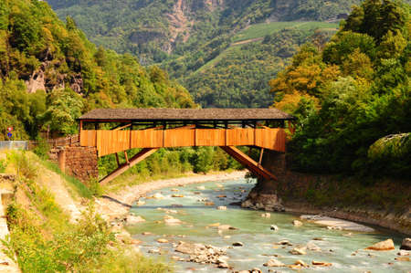 covered bridge: The Wooden Bridge Over the Adige River at the Foot of the Italian Alps