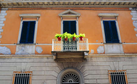 Typical Italian Windows With Closed Wooden Shutters, Decorated With Fresh Flowers photo