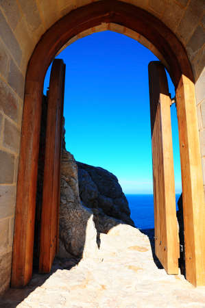 View of the Blue Sky and Sea Through the Gate of the Ancient Fortress on the Island of Rhodes photo
