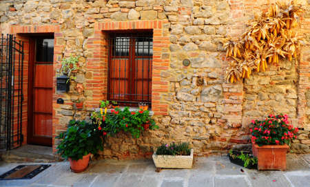 Typical Italian Window and Door Decorated With Fresh Flowers  Stock Photo