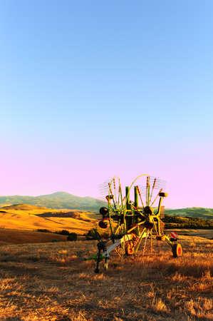 winnowing: Winnowing Machine on The Wavy Hills of Tuscany at Sunset Stock Photo