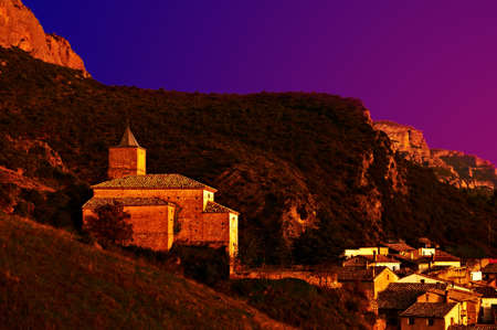 Night Scene of Spanish Medieval Village at the Foot of the Rocks in the Pyrenees photo