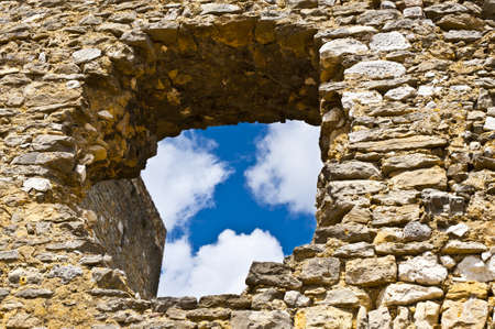 View on a Cloudy Blue Sky through the Hole in the Wall of the Fortress of Saint Montan photo