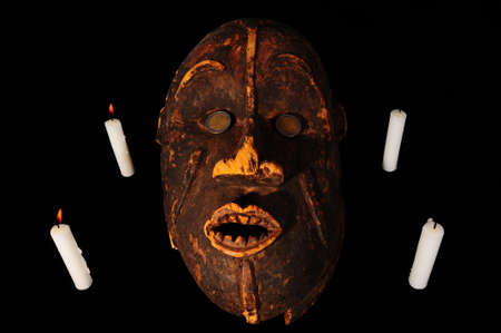 Burning Candles around the Old Wooden African Mask on Black Background photo