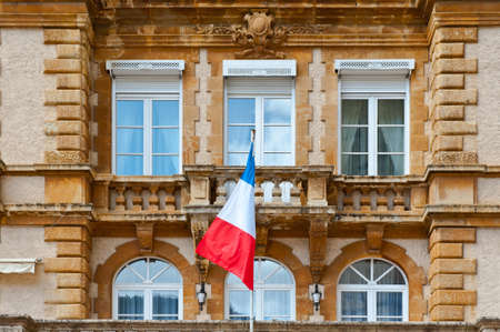French Flag at Facade of Historic Building in city of Mende photo