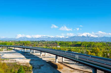 꼭대기가 눈으로 덮인: The Modern Highway in Piedmont on the Background of Snow-capped Alps, Italy