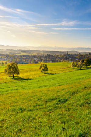 Small Swiss Town Surrounded by Meadows on the Background of Snow-capped Alps, Sunrise photo