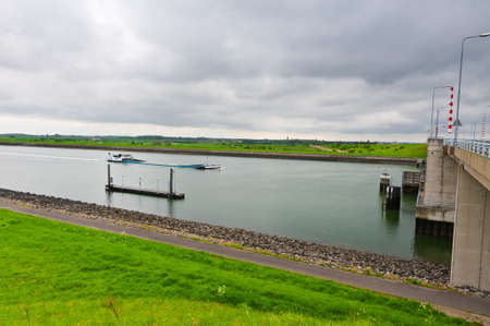 dike: Asphalt Road along Protective Dam and Canal in the Netherlands Stock Photo