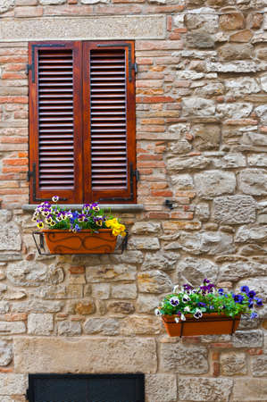 Italian Window with Closed Wooden Shutters, Decorated With Fresh Flowers