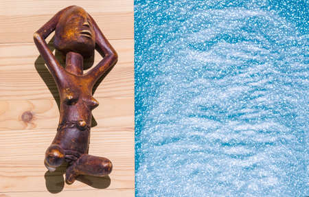 African Wooden Figure Sunbathing on the Beach photo