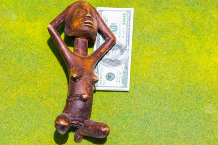 African Wooden Figure Sunbathing on the Green Grass and Dollar photo