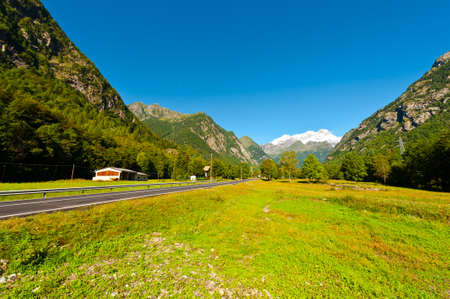 Asphalt Road Leading to the Snowy Peaks of the Alps photo
