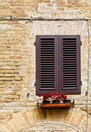 Italian Window with Closed Wooden Shutters, Decorated With Fresh Flowers photo