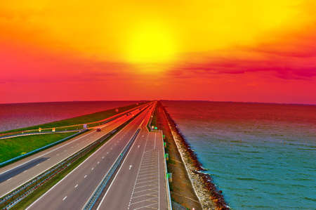 Sunset over Modern Highway on the Protective Dam in Netherlands
