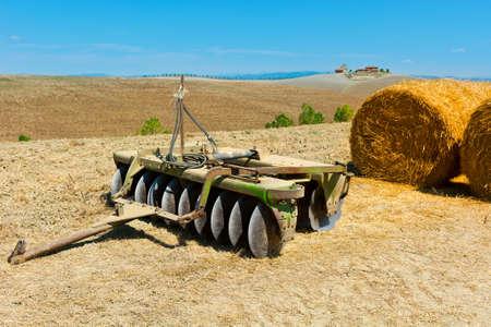 harrow: Landscape with Harrow and Hay Bales in Tuscany Stock Photo