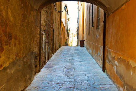 volterra: Narrow Alley with Old Buildings in Italian City of Volterra Stock Photo