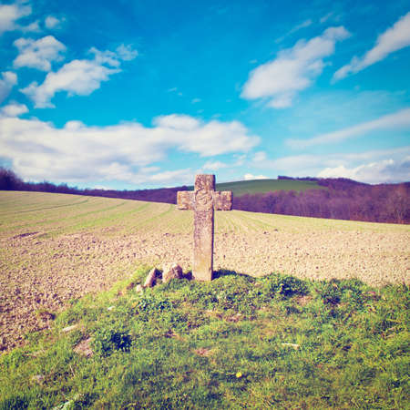 The Medieval Stone Cross on the Plowed Field in Spain, Retro Effect photo