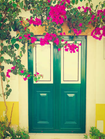 resplendence: Wooden Portuguese Door Decorated with Red Bougainvillaea, Retro Effect Stock Photo