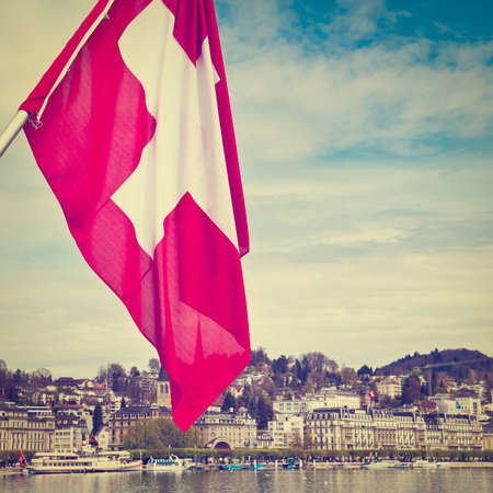 Swiss Flag on the Background of the Embankment of the River Reuss in Lucerne, Retro Effect photo