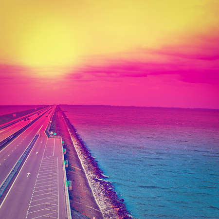 autobahn: Sunset over Modern Highway on the Protective Dam in Netherlands