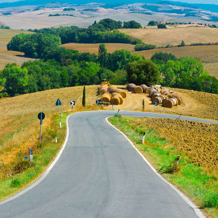 Winding Paved Road between Autumn Plowed Fields in the Tuscany photo