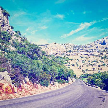 Winding Asphalt Road Leading to the White Spanish City,  photo