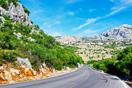 Winding Asphalt Road Leading to the White Spanish City photo