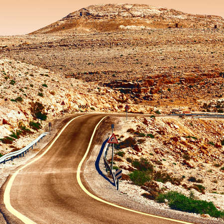 Winding Asphalt Road in the Negev Desert in Israel at Sunset, Vintage Style Toned Picture