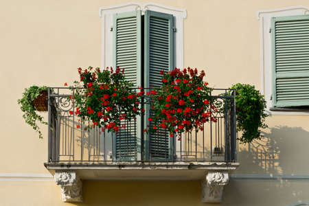 renovated: The Renovated Facade of the Old Italian House with Balcony Decorated with Fresh Flowers