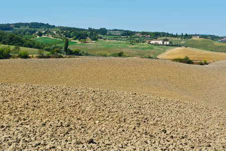 olive groves: Small Medieval Italian Village in Tuscany Surrounded by Plowed Fields, Vineyards and Olive Groves Stock Photo