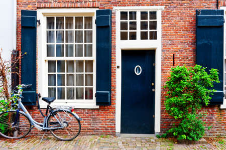 puertas de madera: Bicicleta delante de un ladrillo de la fachada del antiguo Dutch House Foto de archivo