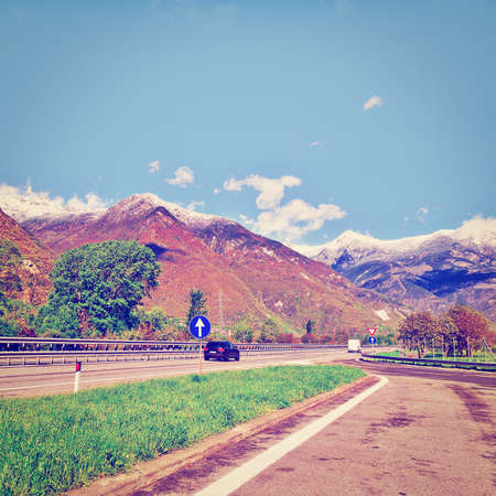 toll: Traffic on Toll Road on the Background of Snow-capped  Italian Alps, Instagram Effect Stock Photo