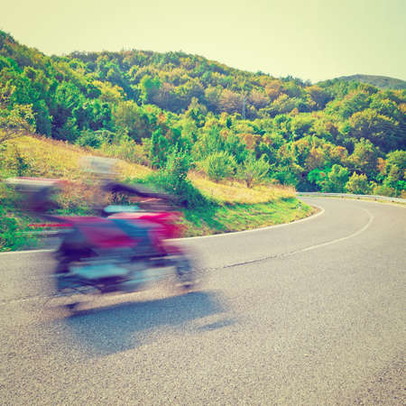 motorcyclist: Motion Blur Motorcyclist on the Winding Asphalt Road in the Italian Alps Stock Photo