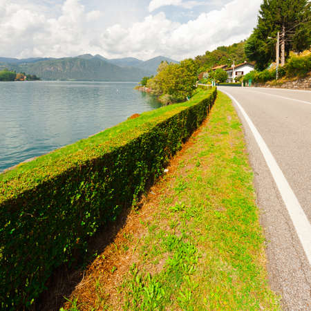 country road: Asphalt Road along the Lake Orta in the Italian Alps Stock Photo