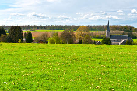 Green Meadow on the Background of the Village Church in Belgium