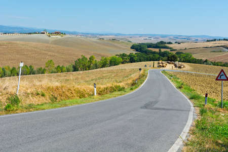 farmhouses: Asphalt Road among Plowed Sloping Hills of Tuscany in the Autumn on the Background of Farmhouses in Italy