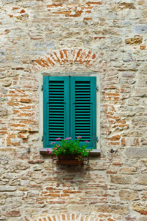 resplendence: Italian Window with Closed Wooden Shutters, Decorated With Fresh Flowers Stock Photo