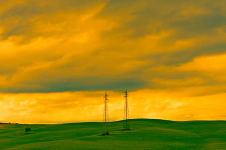 green power: High-voltage Power Line Passes through the Green Sloping Meadows of Tuscany, Vintage Style Toned Picture