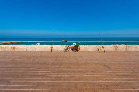 velocipede: Bicycle and Fishing Rod on the Promenade of the Old Port in Tel Aviv Stock Photo