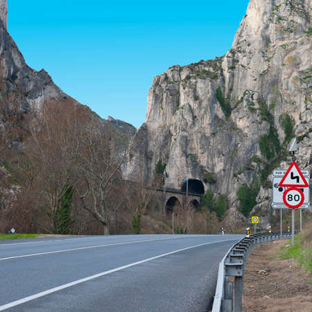 restrictive: Dangerous Curves Sign at the Road Running Along the Railway in the Pyrenees