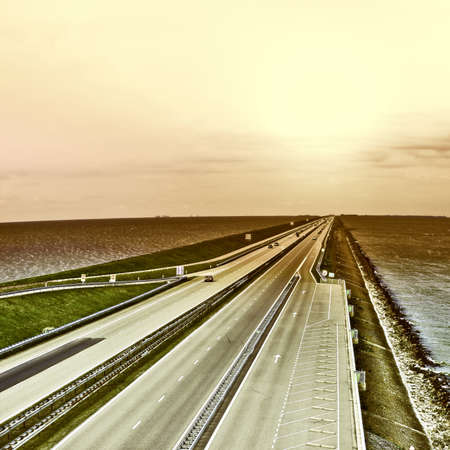 dyke: Sunset over Modern Highway on the Protective Dam in Netherlands, Vintage Style Toned Picture