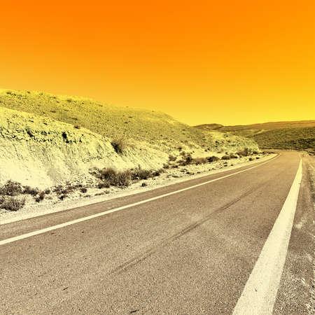 nature reserves of israel: Winding Asphalt Road in the Negev Desert in Israel at Sunset Stock Photo