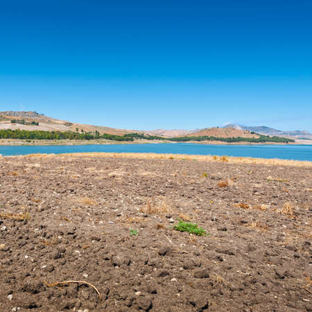 Plowed Shore of the Lake Lago di Ogliastro on the Background of the Mount Etna in Sicily
