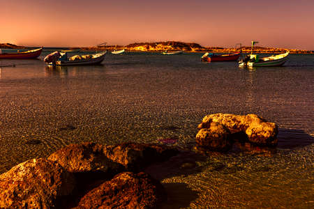 Small motor boats at the beach.  Fishing Boats moored in the mediterranean sea in Israel at Sunset. Stock Photo