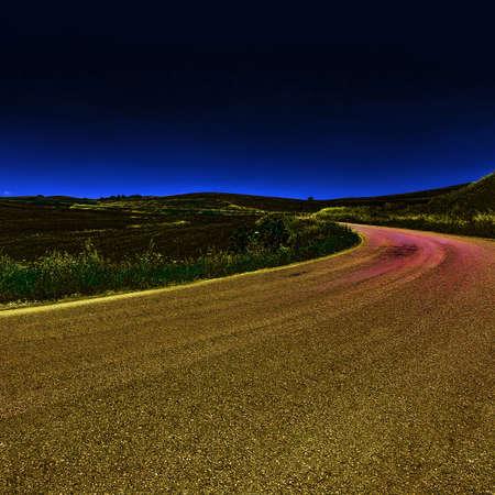 Winding Asphalt Road between Spring Plowed Fields of Sicily at Sunset