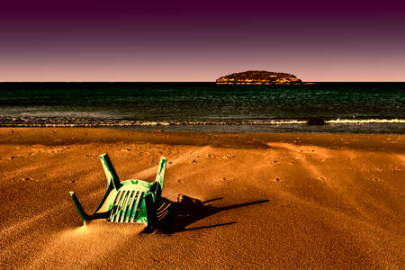 hostile: View of a small island from the Israeli shore of the Mediterranean Sea. Plastic chair buried in the sand of beach in Israel at sunset. Stock Photo