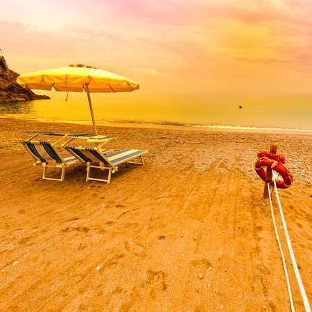 Beach Umbrella and Lifebuoy on the Sandy Coast at Sunrise Stock Photo