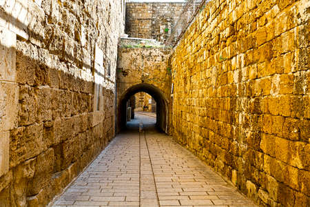 Narrow Alley in the old city of Akko in Israel.  Cobbled street among traditional stoned houses in old Acre.
